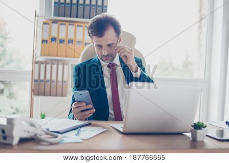 Businessman Realtor  Is Concentrated And Typing A Message On His Smart Phone In Office. He Is In A S