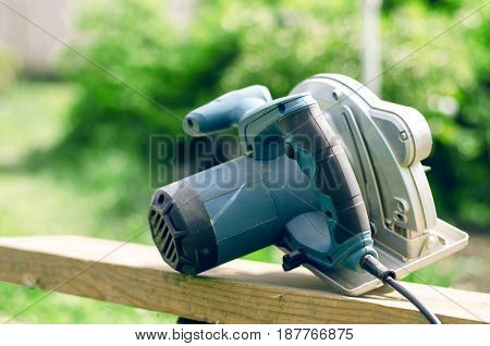 Circular saw and  wooden beam. Electric tools.