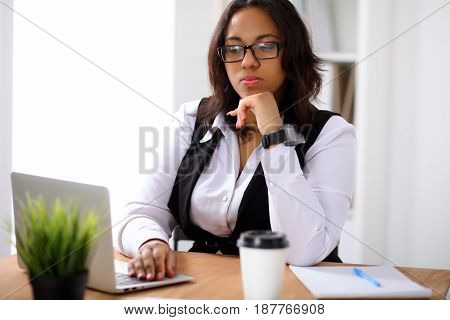 African american business woman is busy with laptop in office while sun shines outdoors
