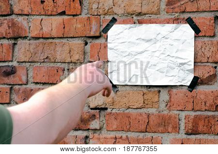 Blank paper page. Man hand shows on clean handbill on brick wall. Advertising concept.