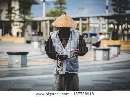 Japanese man standing at front station for receive donation from people, Japan