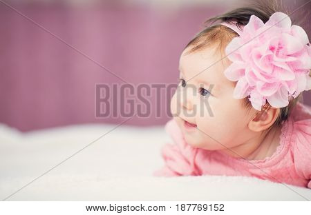 Cute little baby girl lying in the bed in pink dress. Three month old infant child on white soft blanket