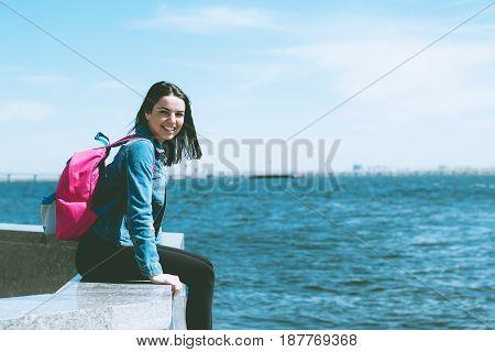 Beautiful Girl Sits On Parapet Near Water