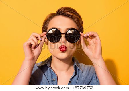 Kiss For You! Fashionable Young Cute Girl In Trendy Sunglasses Sends A Kiss Against Bright Yellow Ba