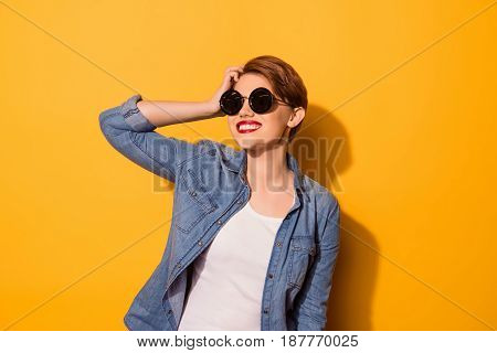 Young Cute Lady With Beaming Smile In Stylish Spectacles Is Fixing Her Hair On The Bright Yellow Bac