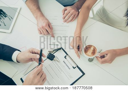 Close up photo of man's hands reading an agreemant of buying a property. Broker giving some advice about new purchase