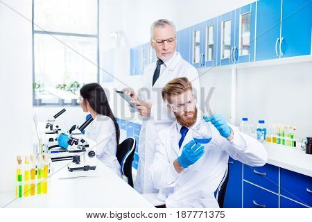 Laboratory Group Of Three Is Working For New Project. Young Bearded Stylish Intern Is Looking At The