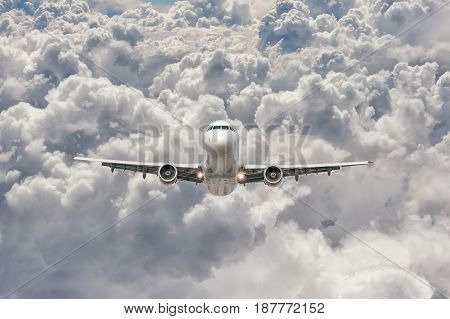 front view of a big jet plane flying through the clouds