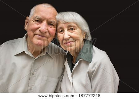 The happy elderly couple on the black background