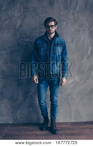 Autumn. Young Serious Bearded Guy In Casual Jeans Outfit Is Standing On A Concrete Wall`s Background