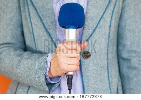Reporter holding microphone. Media reporting. Journalism. News.