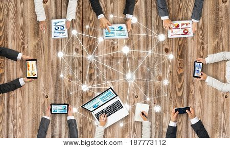 Group of people with devices in hands working together as symbol of networking and communication
