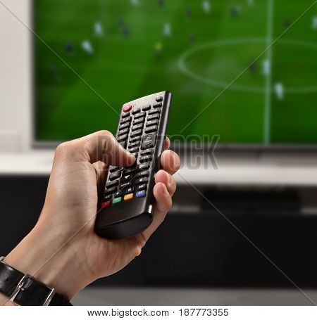 Watching football game hand holding television remote control.