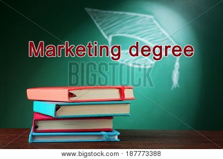 Marketing degree concept. Books on wooden table against blackboard background