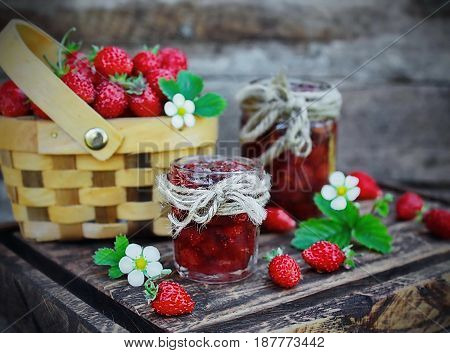 jam from wild strawberries, fresh berries and flowers on wooden Board