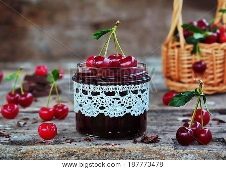 cherry jam with the chocolate in a glass jar and fresh cherries