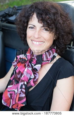 Middle-aged Woman With A Pink Scarf Sitting In A Convertible Car