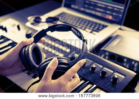 Sound Engineer is picking headphone to start mixing song.
