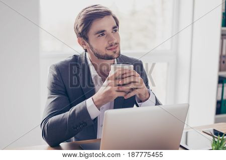 Young Dreaming Worker Is Thinking In Front Of Laptop At Work Place. He Is Happy, Smiling And Holding