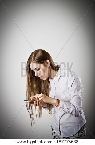 Woman in white is using a mobile phone.