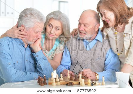 Old people play chess at the table