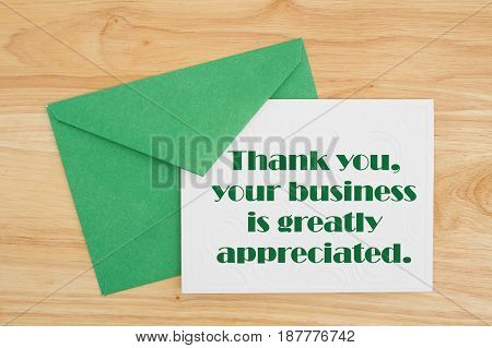 Thank You message An embossed white card with green envelope on wood with text Thank You your business is greatly appreciated