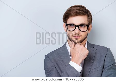 Confident Pensive Handsome Bearded Young Man Is Looking Away Wearing Suit And Glasses. Touching His