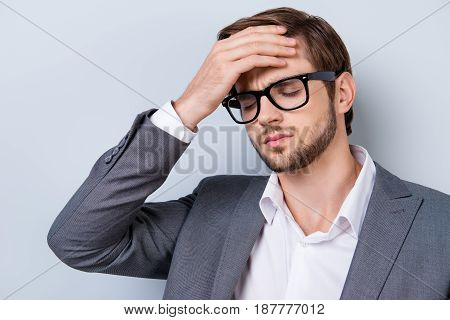 Close Up Portrait Of Tired Sick Handsome Young Man Touching His Forehead. He Is Wearing The Formalwe