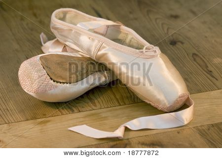 A pair of discarded ballet shoes on wooden dance studio floor