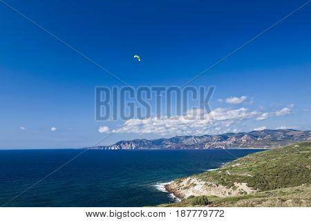 Colorful hang glider in sky over Mediterranean blue sea. Sardinia west coast