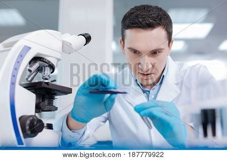 Try to be serious. Dark-haired man leaning arms on the table, keeping test-tubes in both hands while looking at the process