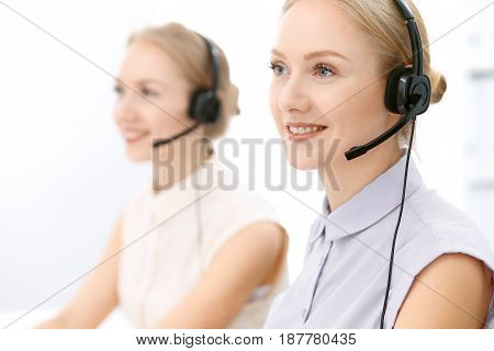 Call center at busy day. Focus on beautiful blonde woman in headset while consulting customers.