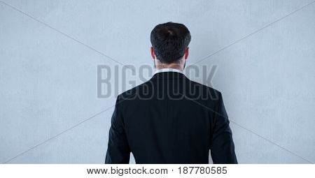 Digital composite of Rear view of businessman standing against blue background