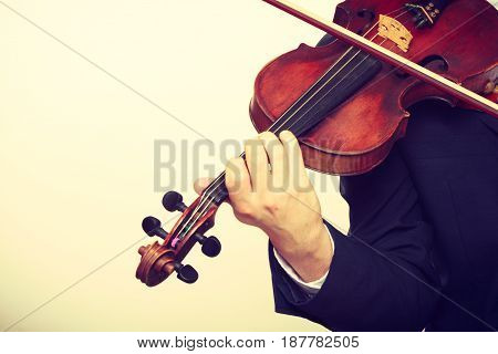 Music passion hobby concept. Close up of young man man dressed elegantly playing on wooden violin. Studio shot on white background
