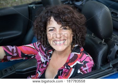 a woman sitting in a convertible car