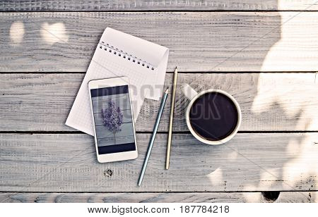 Cup of coffee notepad phone with photo of lilac branch on the white wooden table