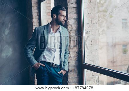 Success Concept. Stylish Young Bearded Man Is Standing Near The Window And Looking Far. He Is In A S