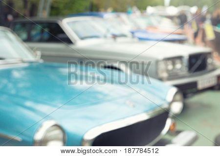 Defocused photo of retro car show exhibition