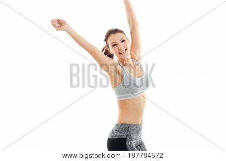 fun energetic girl in grey top with beautiful breasts laughs and raises her hands up isolated on white background