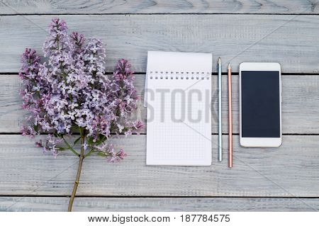 Notepad phone and a lilac branch on the white wooden table