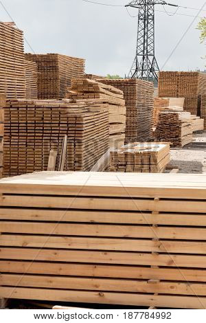 lumber boards and beams lie in a pile at the sawmill