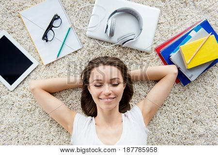 Above Top View Photo Of Young Relaxed Student With Closed Eyes Lying On A Carpet And Dreaming On The