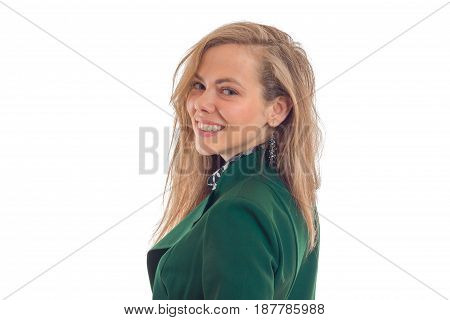 Portrait of a beautiful young blonde in a green jacket that stands sideways looks straight and smiling isolated on white background