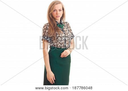 young sexy blonde stands in blouse and green skirt and looks into a camera isolated on white background