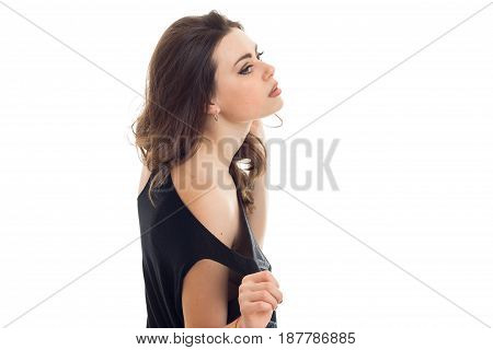 beautiful young brunette stands sideways in front of the camera holding up head close-up isolated on white background