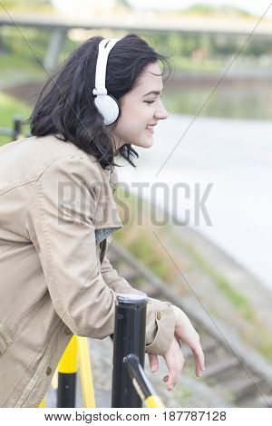 Young Beautiful Woman Standing By The River, Listening To Music And Enjoying The Beautiful View