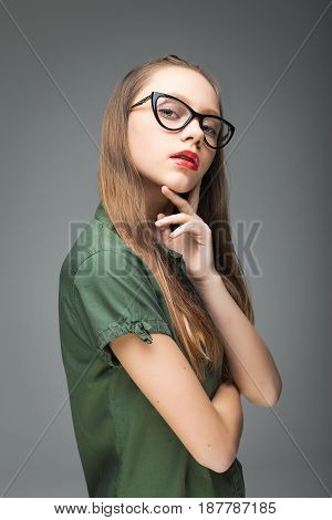 Portrait of young cute spectacled girl over gray background. woman dressed in green T-shirt