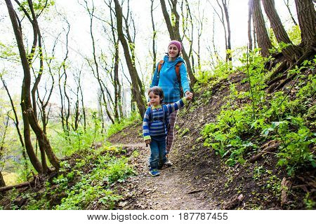 The Boy And His Mother Are Walking Through The Woods.