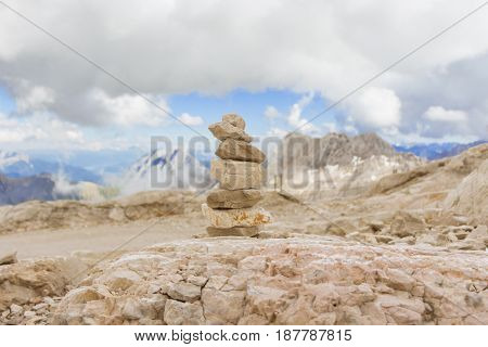 Little stone tower in climate change cold to warm mountains. Stones stack in mountain panorama with blue sky visualizes creativity consulting success or showing health meditation and therapy.