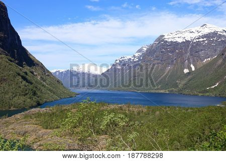 A Beautiful Spring Day With Snow On The Mountain Peaks, Blue Sky And Green Hills In Loen In Stryn.